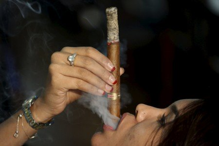 Francis Sierra smokes as she competes for the longest ash during the XVIII Habanos Festival in Havana